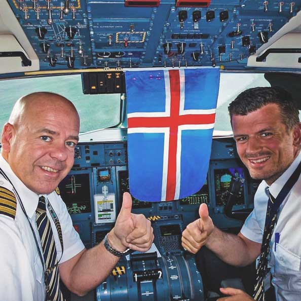 Pilots in the cockpit smiling giving thumbs up with the Icelandic Flag in between them
